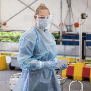 En sjukskötare i skyddsutrustning står vid en bil i en drive-in-coronateststation.