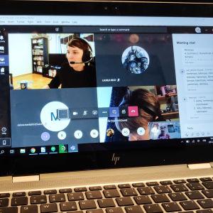 En bärbar dator på en soffa. På skärmen syns flera personer och en chattruta.