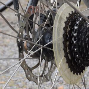 Närbild av bromsskivan på en cykel och bakväxeln.