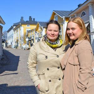 Två unga kvinnor i beige jackor står i gamla stan i Borgå. De tittar in i kameran och ler. Bakom dem synns en kullerstensgata och trähus i olika färger.
