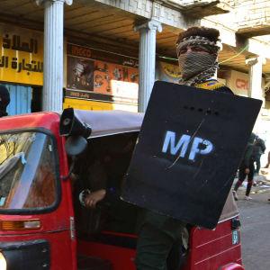 En demonstrant som utrustat sig med en sköld åker Riksha i Bagdad.