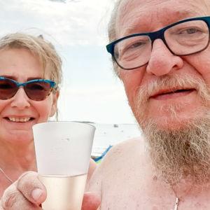 Kuusikymppiset mies ja nainen poseeraavat kameralle ranta-asuissa kuohuviinilaseja kohottaen. Taustalla näkyy meri.