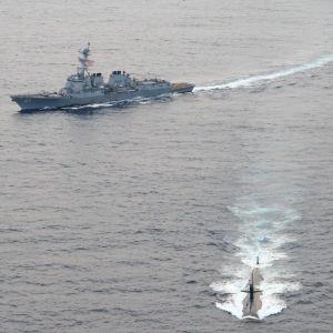 En amerikansk atomubåt av klassen Los Angeles, med två örlogsfartyg i bakgrunden.