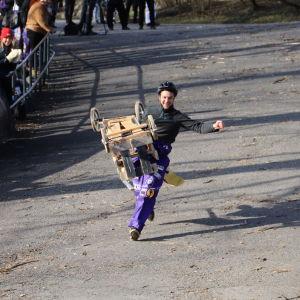 En man springer ner för backen bärandes på en pulkka.