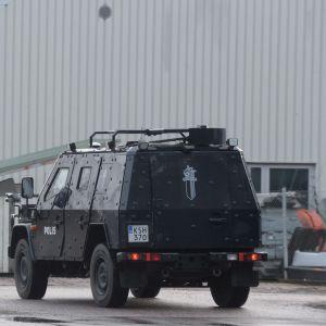 Två polisbilar utanför en grå fabrik. Ena är ett pansarfordon.