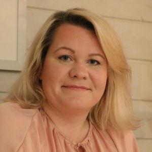En kvinna med axellångt blont hår sitter på en bänk. Bakom henne på väggen skymtar en tavla.