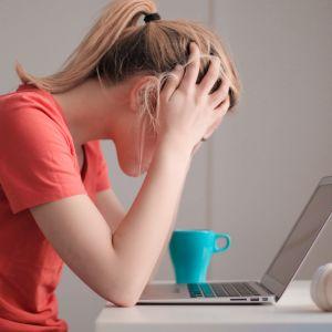 Kvinna i röd t-shirt sitter vid ett bord med uppfälld laptop och lutar huvudet i händerna