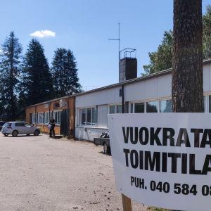I högra hörnet på bilden syns en skylt där det står på finska att affärsutrymmen uthyres. Bkom skylten synns ett lågt långt hus.