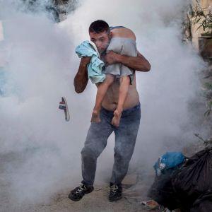 Man som bär på ett barn i flyktingläger på Lesbos