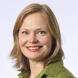 Porträtt bild av riksdagsledamot Hanna Kosonen. Hon är klädd i grön skjorta och är fotad mot vit bakgrund.