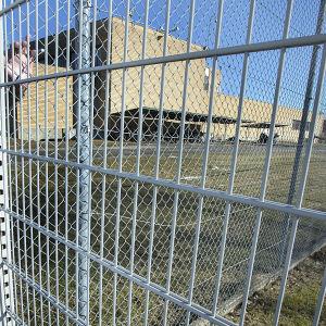 Direktören för Tavastehus fängelse Samuli Laulumaa står lutad mot fängelsets gallerstaket.