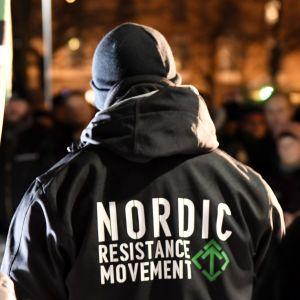 Nordiska motståndsrörelsens marsch i Helsingfors på självständighetsdagen 2017. En man har på sig en jacka med organisationens namn tryckt på ryggen.