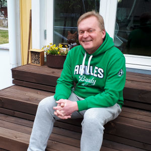 En man i grön munkjacka sitter på en hustrappa.