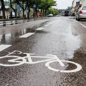 Bild på Ågatan i Borgå. På gatan har man med vitt målat vita linjer och bilder på cyklar på båda sidorna av körbanan.