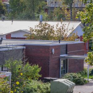 En tegelbyggnad med platt tak fotad lite högre upp ifrån så att taket syns.