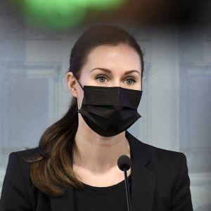 Sanna Marin håller presskonferens 9.4.2021. Hon bär ett svart munskydd.