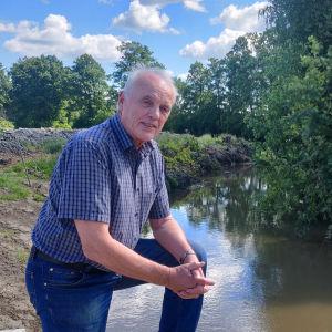 Yle / Mira BäckEn äldre man står på knä invid en å. Närbild.