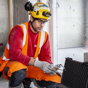En man med skyddshjälm och glasögon samt reflexväst sitter på huk på ett betonggolv med en fuktighetsmätare i handen.