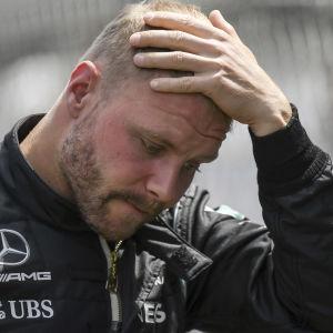 Valtteri Bottas sätter sin handflata mot sitt nedböjda huvud, iklädd Mercedes svarta tävlingsdräkt.