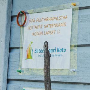 Ljusblå husvägg med skylt där det står att trädgårdsodlingen handhas av daghemsgruppen Sateenkaari Koto.