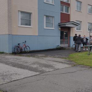 Invånare i ett våningshus står ute på gården.