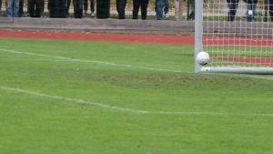 Fotboll går in i mål vid stolproten.