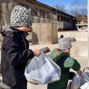 Två barn tar emot veckans skollunchpåse som delas ut i deras skola i Tallinn under coronapandemin.
