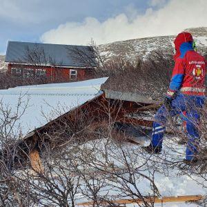Räddningspersonal tittar på ett tak som blåst av i Svinadalur på Island.