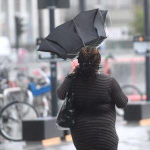 En kvinna går på gatan i grått regnväder. Hennes paraply står rakt upp efter att ha gått sönder.