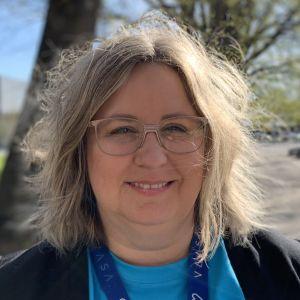 Kvinna står utomhus i vårgrönska, iklädd blus med Vasa stads logo.