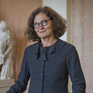 Ebba Witt-Brattström i Helsingfors 2012. Står vid räcke inomhus med staty i bakgrunden.