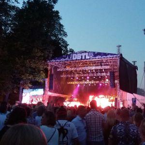 Huvudscenen på musikfestivalen Down By The Laituri i Åbo där bokstäverna DBTL lyser i sommarskymningen.