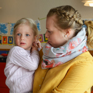 Dagislärare håller två-årig flicka i famnen