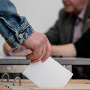 En väljare sätter sin röst i valurnan.