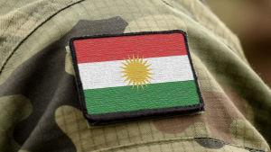 Kurdistans randiga röd-vit-gröna flagga med en gul sol i mitten.