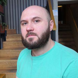 Bild på man i turkos t-skjorta. Han har skägg och är skallig. Han ser bister ut och i bakgrunden skymtar grönväxter och en trappa.