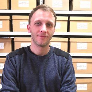 En leende man står framför en hylla med arkiveringslådor.