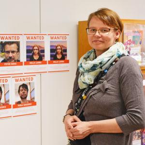 En kvinna står framför en vägg med bilder på misstänkta personer.