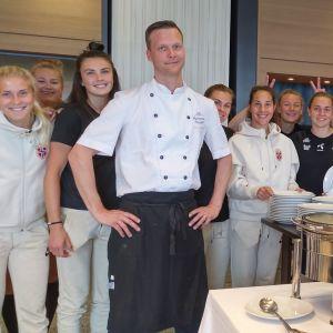 Anders Svahnström iklädd kockdräkt står tillsammans med en del av det norska damlandslaget i fotboll.