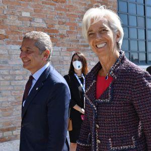 Europeiska centralbankens chef Christine Lagarde ler, omgiven av män i kostym.