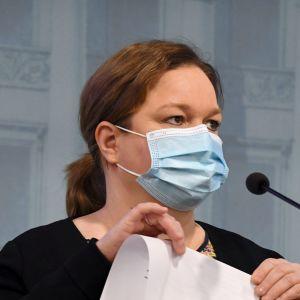 En kvinna i blått munskydd står vid en mikrofon. Hon är klädd i svart tröja och har håret i en hästsvans. I händerna har hon ett pappersark som hon viker på mitten.