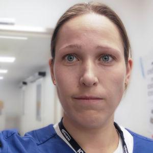 En  kvinna i läkarkläder i en vit korridor