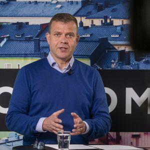 Petteri Orpo i blå ylletröja talar till en kamera.