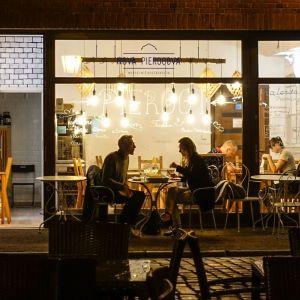 En restaurang fotograferad genom ett fönster. Två par syns äta mat vid separata bord.