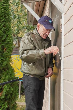 Mies korjaa pienen mökin oven salpaa.