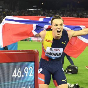 Karsten Warholm jublar med norska flaggan framför en resultatskärm som berättar om hans supertid.