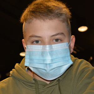 Anton Andersson, en ung pojke med kort ljust hår, ljusblått munskydd och en grön munkjacka tittar rakt in i kameran.