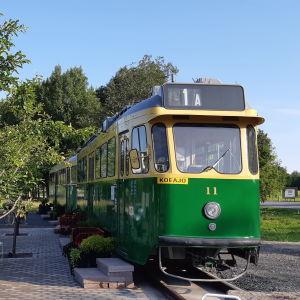 Vanha raitiovaunu 1950-luvulta Mikkelipuistossa ja vieressä raitiovaunun merkki.