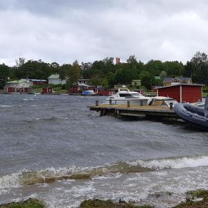 En strand med några båtar och en brygga. Det blåser hårt i det gråa havet.