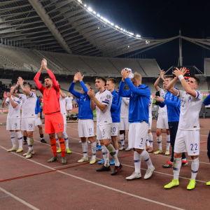 Finlands fotbollsherrar står på rad och applåderar publiken.